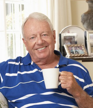 42164508 - retired senior man sitting on sofa drinking tea at home