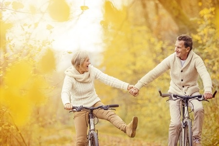 34112000 - active seniors riding bike in autumn nature. they relax outdoor.