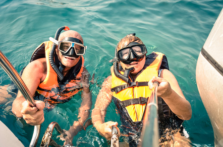 36549929 - senior happy couple using selfie stick in tropical sea excursion - boat trip snorkeling in exotic scenarios - concept of active elderly and fun around the world - soft vintage filtered look