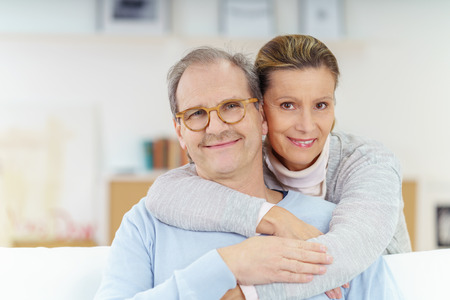 51788398 - smiling couple in their fifties relaxing and embracing at home